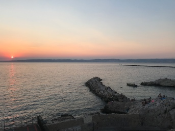 The rocky peninsula was covered with swimmers at sunset.