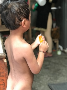 This adorable little one kept running into the home/store to buy whatever sweet, orange treat you see in his hand. Then, naked, he'd run back down to the hot springs.