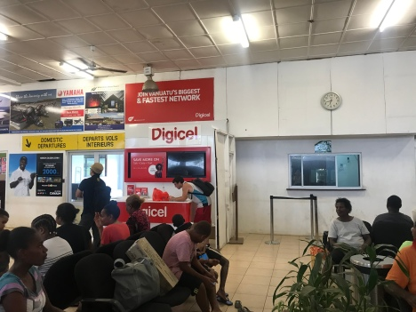 "To the right of the ""digicel"" sign is the counter where you take your boarding pass to pay the 200vt tax."
